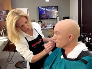 Deborah Paulmann Applying Makeup to Bald Man